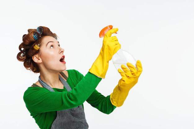 Молодая женщина использует спрей во время уборки дома Бесплатные Фотографии