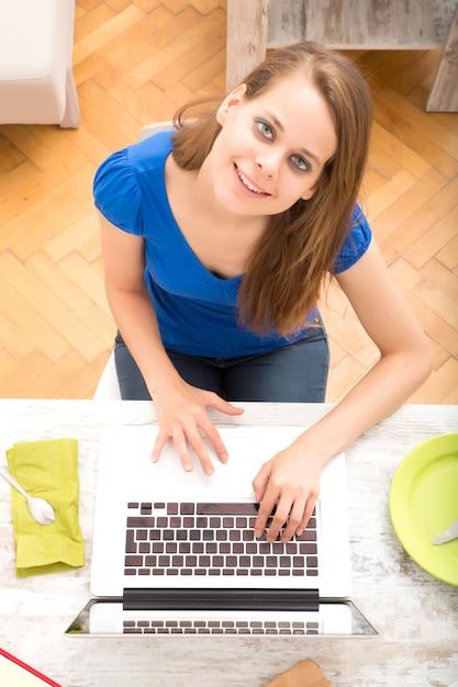 朝食を食べた後、ラップトップコンピューターを使用して若い女性 Premium写真