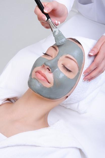 Giovane donna utilizzando la procedura cosmetica nel salone di bellezza Foto Gratuite