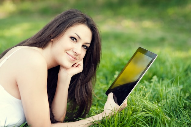 Giovane donna con tavoletta digitale sul prato Foto Gratuite