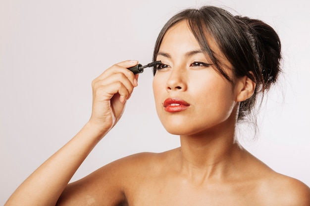 Young woman using eyeliner Free Photo