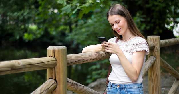 Young woman using her smartphone in a park Premium Photo