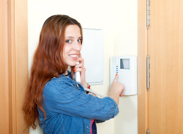 Young woman using house videophone indoor Free Photo