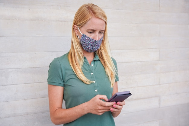 Young woman using mobile phone while wearing face mask during coronavirus outbreak Premium Photo