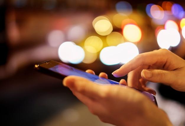 夜の都市でボケ光と携帯電話を使用している若い女性 Premium写真