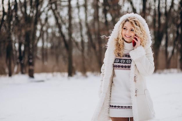 겨울 공원에서 전화를 사용 하여 젊은 여자 무료 사진