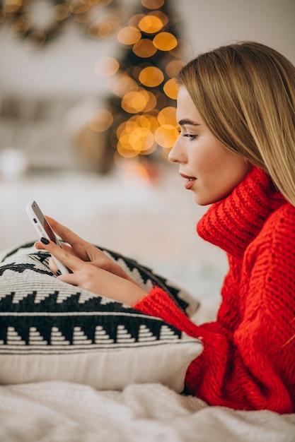 크리스마스에 전화를 사용 하여 젊은 여자 무료 사진