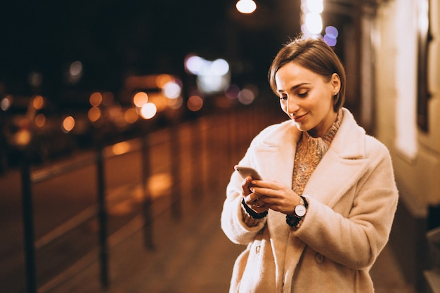 Young woman using phone outside the night street Free Photo