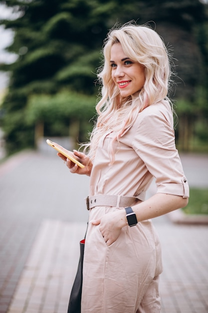 Young woman using phone outside in park Free Photo
