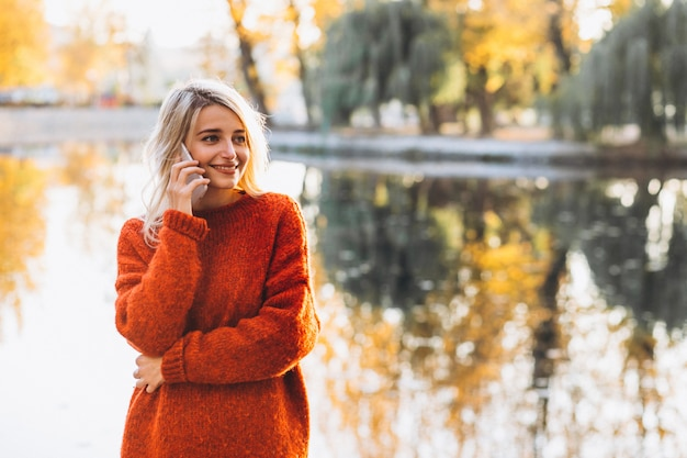 Young woman using phone in park by the lake Free Photo