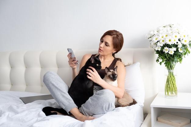 花と一緒に寝室に座っている彼女の2匹の猫と電話を使用している若い女性。 Premium写真
