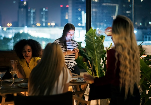Young woman using a smartphone at a dinner night having no interaction with friends Premium Photo