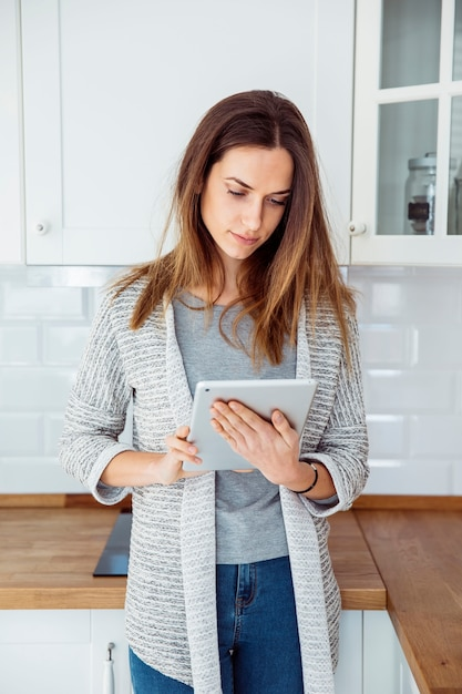 Young woman using tablet in kitchen Free Photo