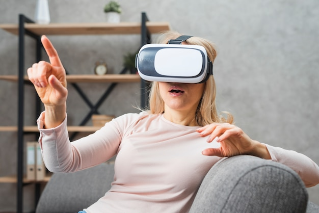 Young woman using a virtual reality headset pointing her finger at something Free Photo