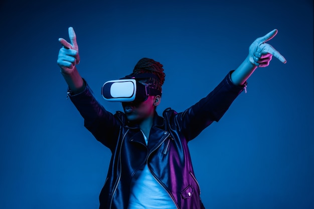 Young woman using vr-glasses with neon lights Free Photo