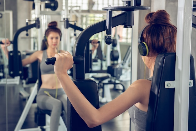 Young woman using weight lifting equipment to build a massive chest and arm at indoor sport gym. Premium Photo