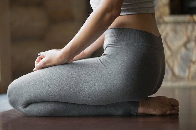 Young woman in vajrasana pose, home interior background, closeup Free Photo