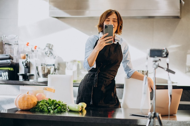 Young woman videoblogger cooking at the kitchen and filming Free Photo
