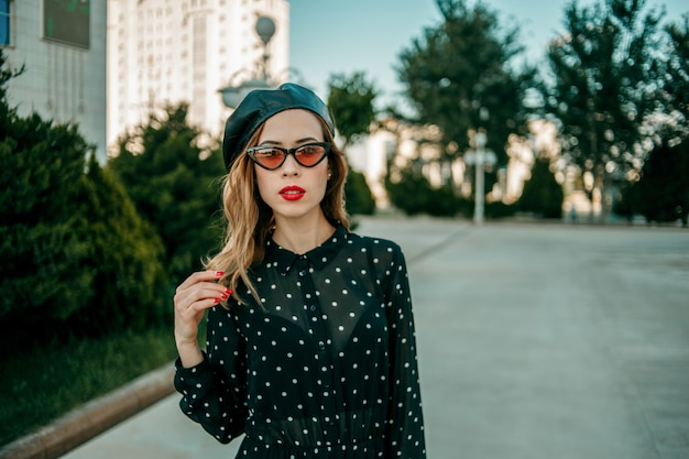 Young woman in vintage black polka dot dress posing outside Premium Photo