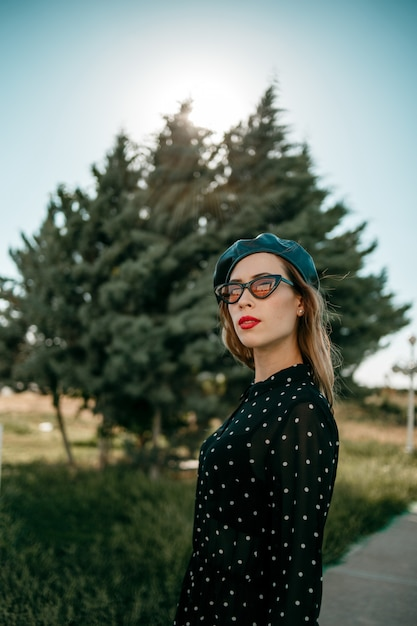 Young woman in vintage black polka dot dress posing outside Premium Photo