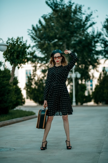 Young woman in vintage black polka dot dress with retro suitcase in hand posing outside Premium Photo
