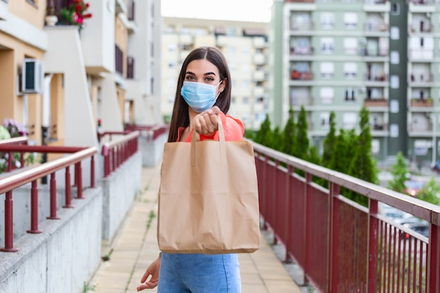 Young woman volunteer with a medical mask is holding a paper bag with food and vegetables. donation, helping people in quarantine, coronavirus. Premium Photo