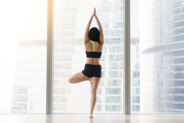 Young woman in vrksasana pose against floor window, rear view Free Photo