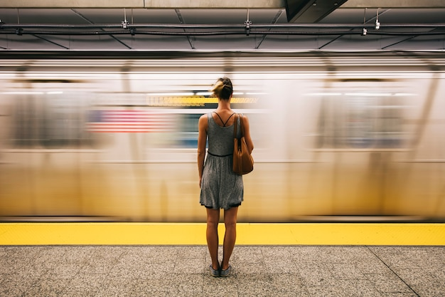 Young woman waiting for subway train in new york city Premium Photo