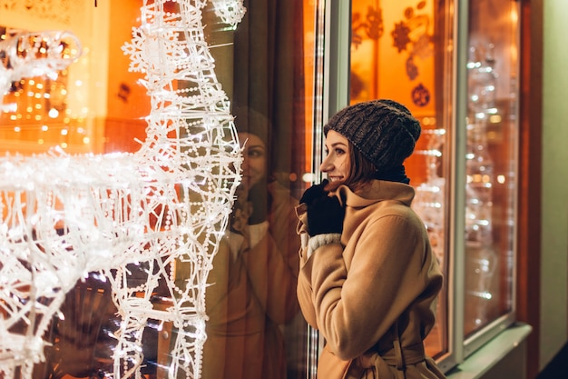 Young woman walking in city and looking at decorated christmas showcases at night. Premium Photo