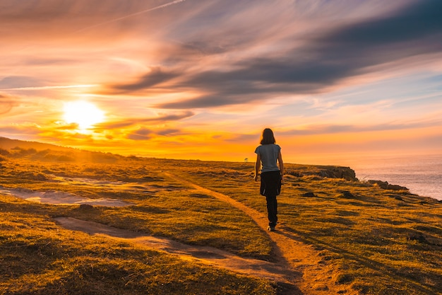 A young woman walking in the sunset of jaizkibel. basque country Premium Photo