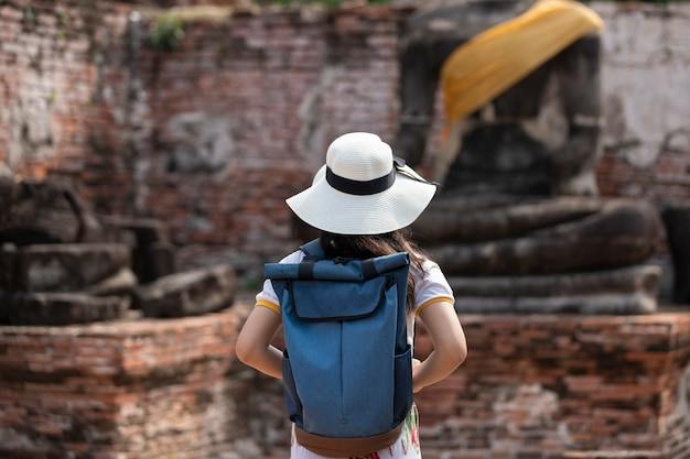 A young woman walks in the old temple in phra nakhon si ayutthaya, thailand on a relaxing day. Premium Photo