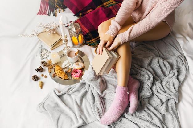 Giovane donna in abiti di lana caldi è seduta sul suo letto in una luminosa casa soleggiata Foto Gratuite
