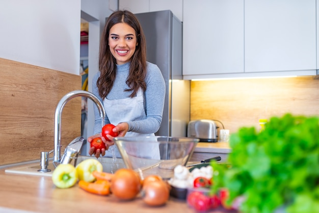Young woman washes the vegetables in domestic kitchen Premium Photo