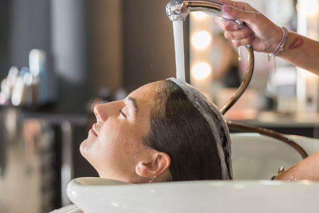 Young woman washing hair in salon Premium Photo