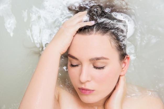 Young woman washing hair. shampoo and foam on black woman's hair. Premium Photo