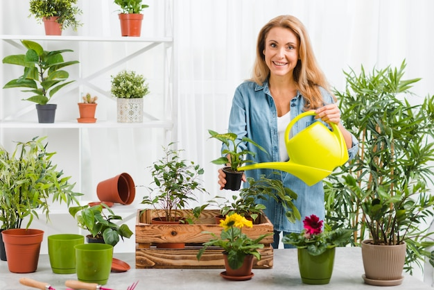 Young woman watering flowers Free Photo