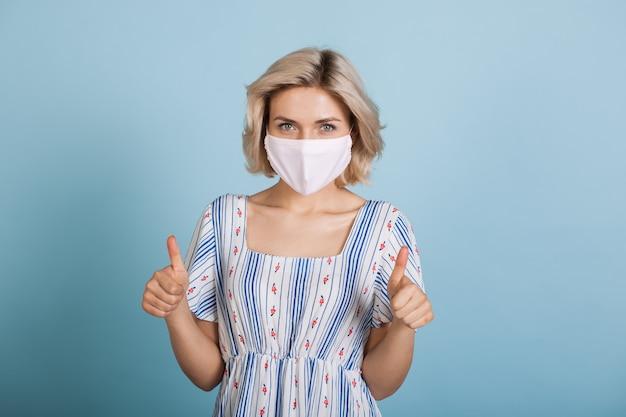 파란색 스튜디오 벽에 같은 기호를 몸짓으로 독감 마스크와 드레스를 입고 젊은 여자 프리미엄 사진