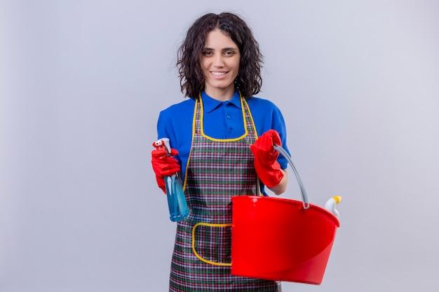 クリーニングツールとバケツを保持しているスプレーエプロンとゴム手袋を着用して若い女性スプレースプレー肯定的で幸せな白い壁 無料写真