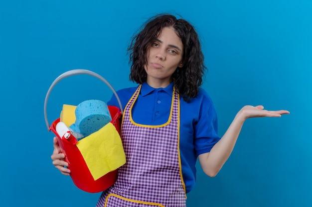 Young woman wearing apron holding bucket with cleaning tools looking confused having no answer standing over blue background Free Photo