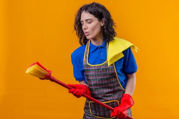 Giovane donna che indossa un grembiule e guanti di gomma tenendo mop utilizzando come microfono cantando una canzone divertendosi in piedi su sfondo arancione Foto Gratuite