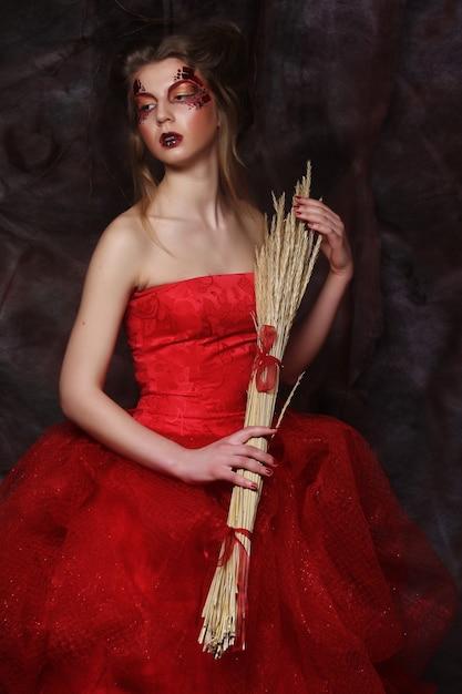 明るいメイクのボールドレスを着て乾いた枝を保持している若い女性 Premium写真