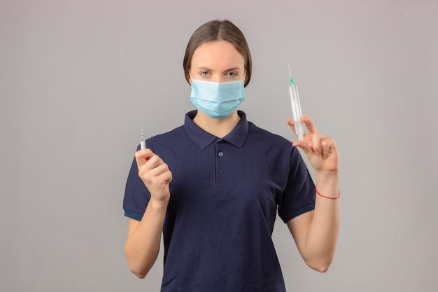 孤立した灰色の背景に深刻な顔立ちでカメラを見て注射器と薬のワクチンの瓶を保持している防護医療マスクで青いポロシャツを着た若い女性 無料写真