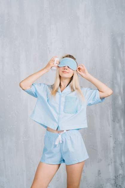 Young woman wearing blue sleeping eye mask in front of wall Free Photo