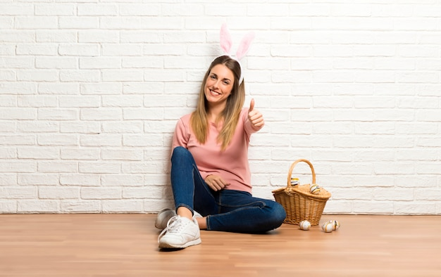 Young woman wearing bunny ears for easter holidays giving a thumbs up gesture and smiling Premium Photo
