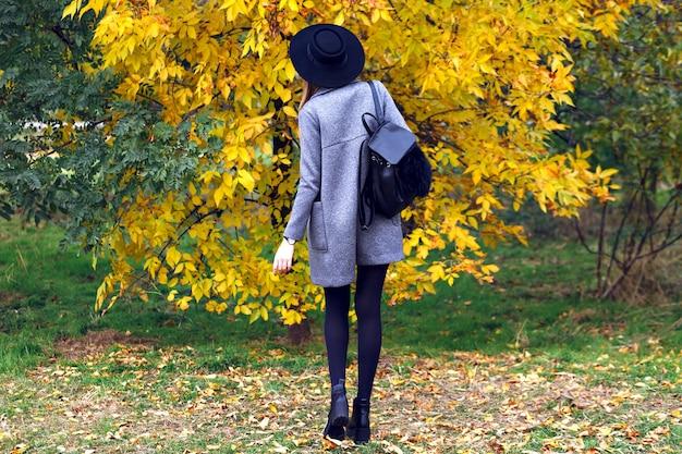 Молодая женщина в повседневной элегантной уличной одежде, шляпе и пальто гуляет в городском парке осеннего дня, позирует обратно. Бесплатные Фотографии