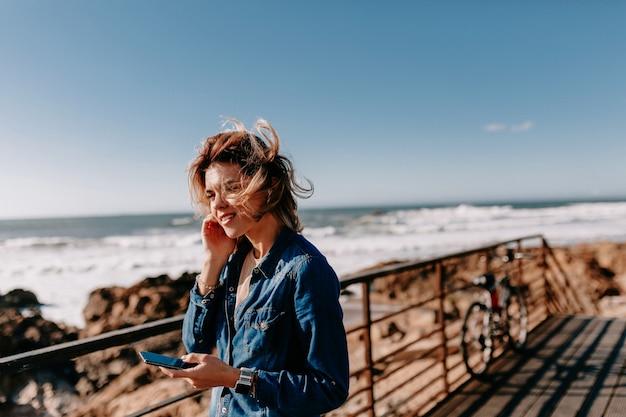 데님 셔츠를 입고 젊은 여자가 해변에서 포즈를 취하는 전화 통화 무료 사진