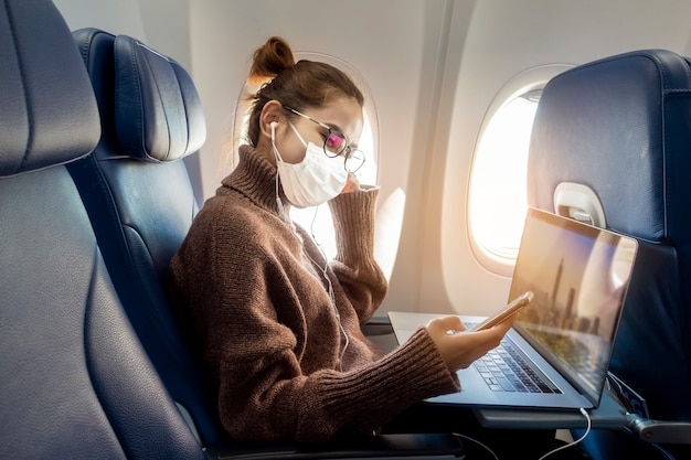 A young woman wearing face mask is traveling on airplane , new normal travel after covid-19 pandemic concept Premium Photo