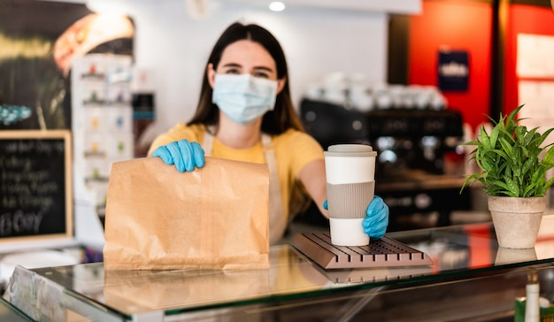 Young woman wearing face mask while serving takeaway breakfast and coffee inside cafeteria restaurant Premium Photo