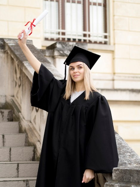 Young woman wearing graduation gown Free Photo
