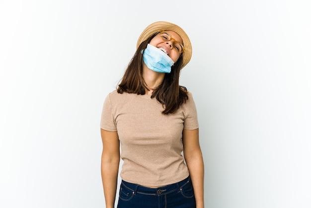 Молодая женщина в шляпе и маске для защиты от covid изолирована на белой стене расслабленно и счастливо смеется, вытянув шею, показывая зубы Premium Фотографии
